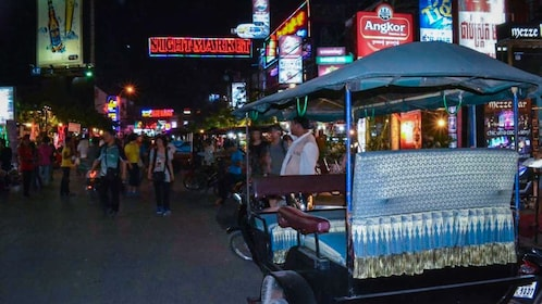 Transportation carriage shown parked on street near night market.