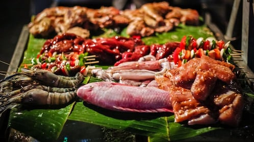 Close up of cooked meat on platter, including shrimp and fish.