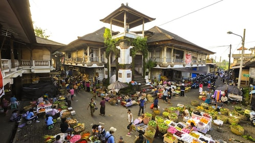 Bali marketplace with stands of fresh produce and residents shopping.