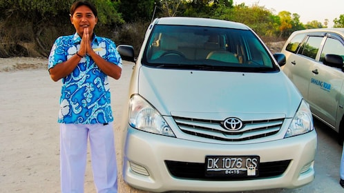 Tour guide standing by parked Toyota.