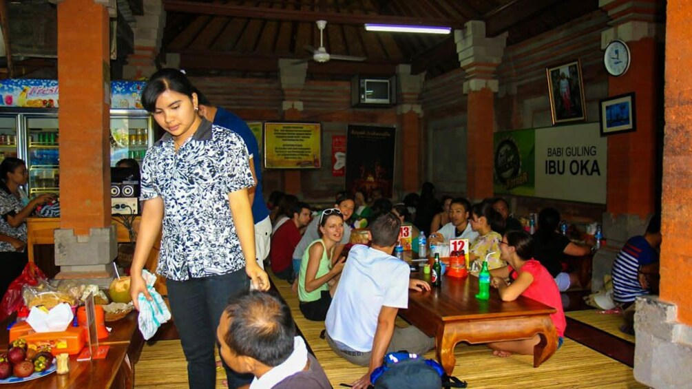 Show item 3 of 8. Tourists in Bali restaurant seated on ground tables ready to eat.
