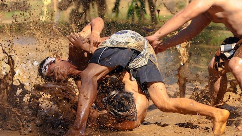 Action shot of two men mud wrestling.