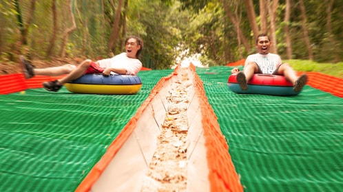 Two people sliding down a hill on inner tubes in Penang