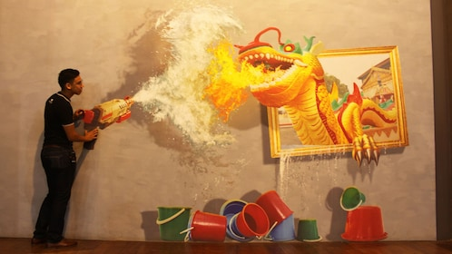 Guy posing infront of an optical illusion painting of a Dragon breathing fire.