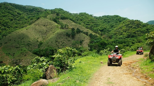 ATV riding group on a dirt road with mountains in the background in Puerto Vallarta
