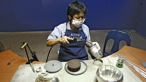 Person taking a blowtorch to a metal bowl in Royal Selangor