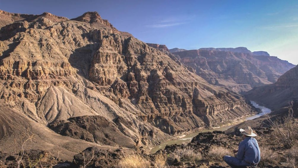 Show item 9 of 9. Landscape view of large canyon with man observing while sitting.