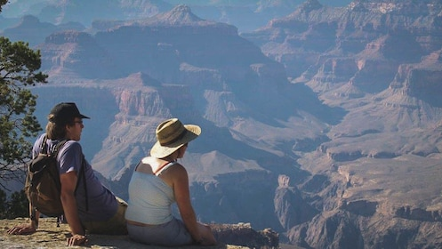 Man and woman sitting on cliff of canyon observing.