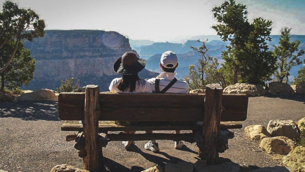 Show item 3 of 9. Man and woman sitting on wooden bench in Grand Canyon, shown from behind.