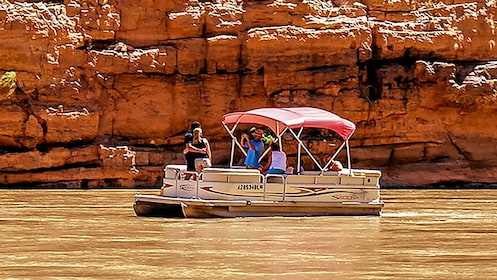 A couple poses for a picture in a boat on the Colorado river in the Grand Canyon