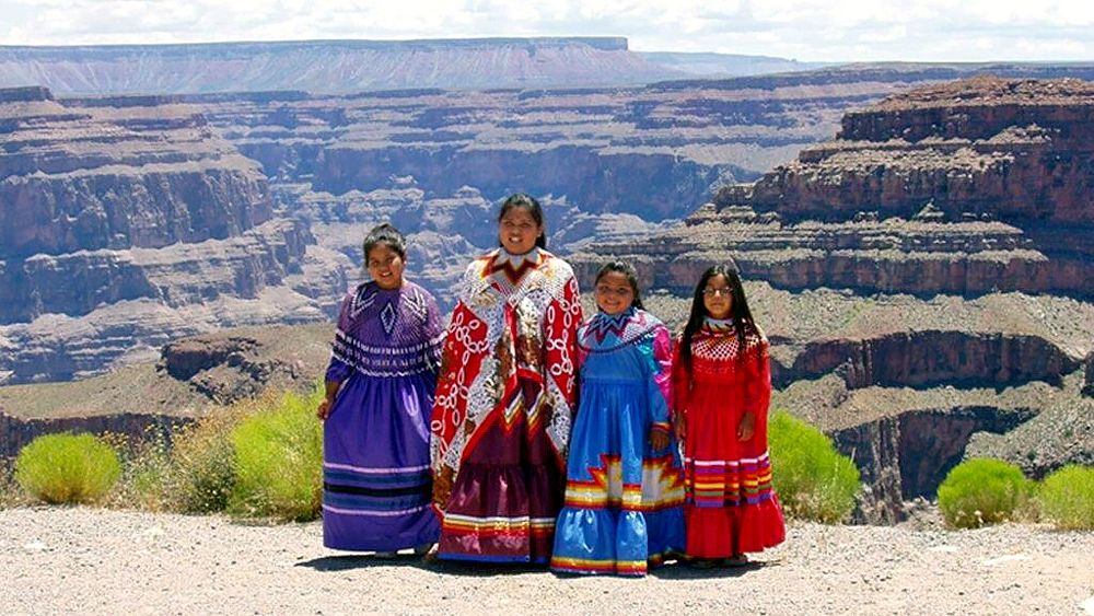 Four members of the Havasupai Tribe posing in front of the grand canyon