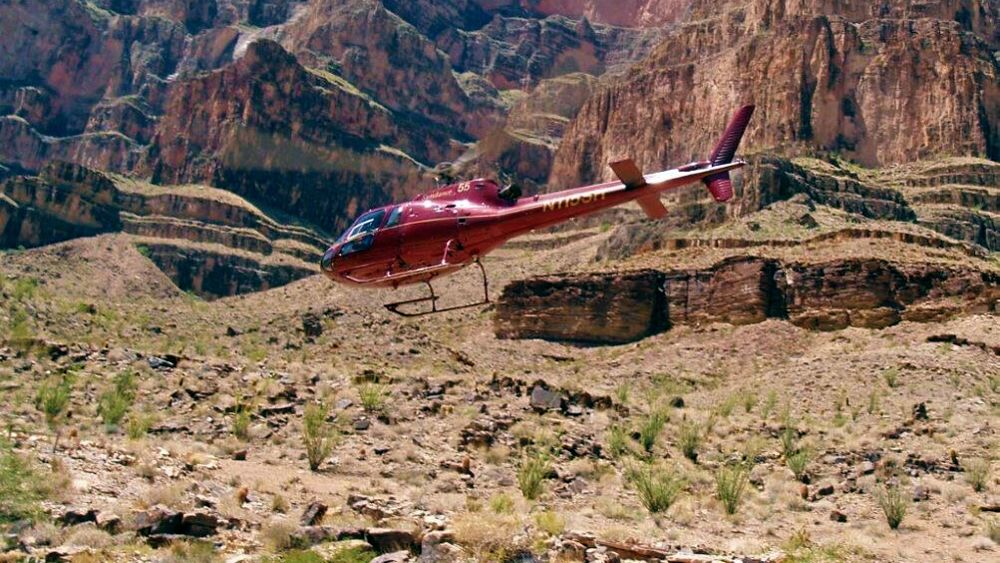 A helicopter hovering over the Grand Canyon