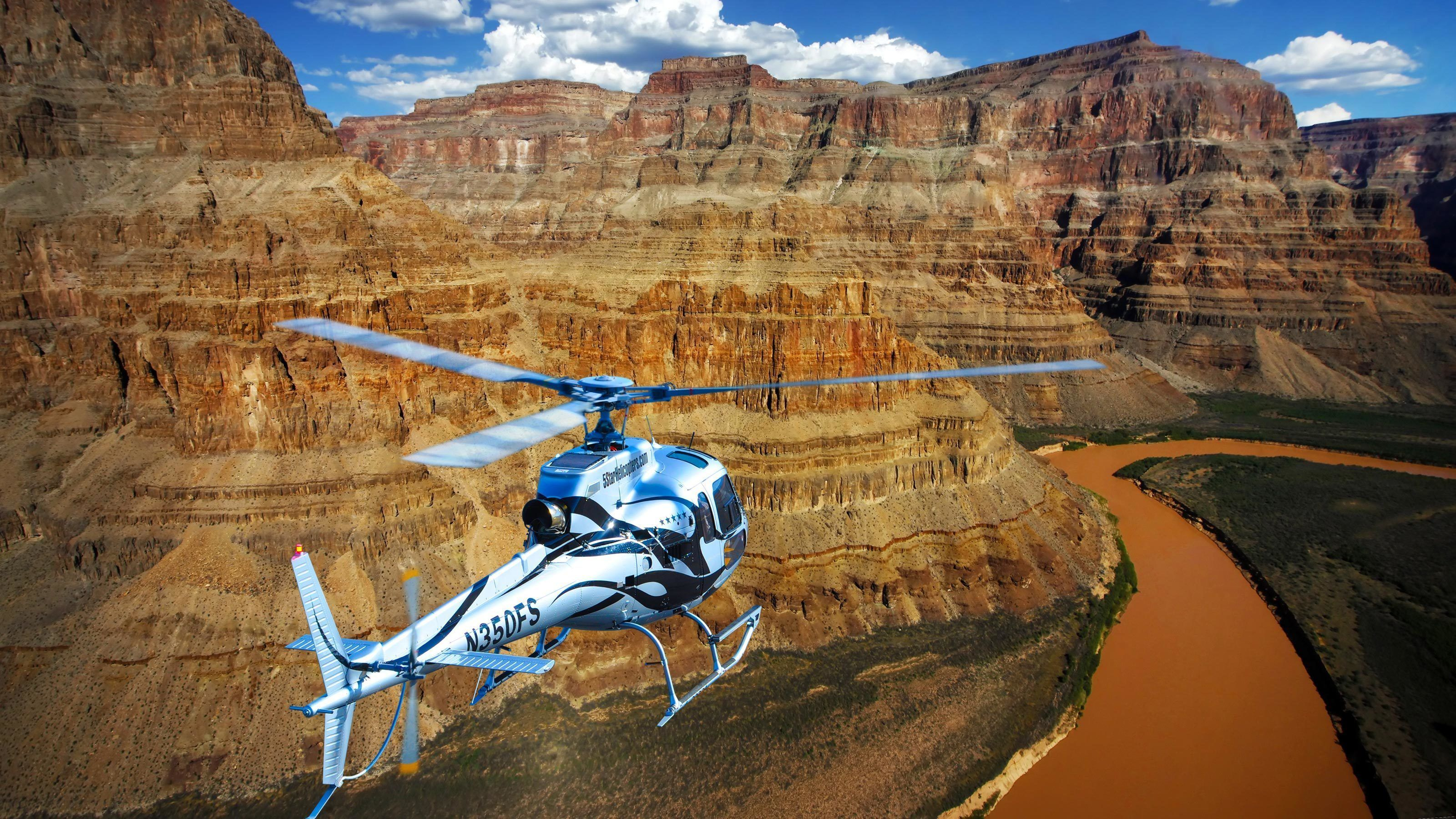 Helicopter hovers over the Colorado river in the Grand Canyon