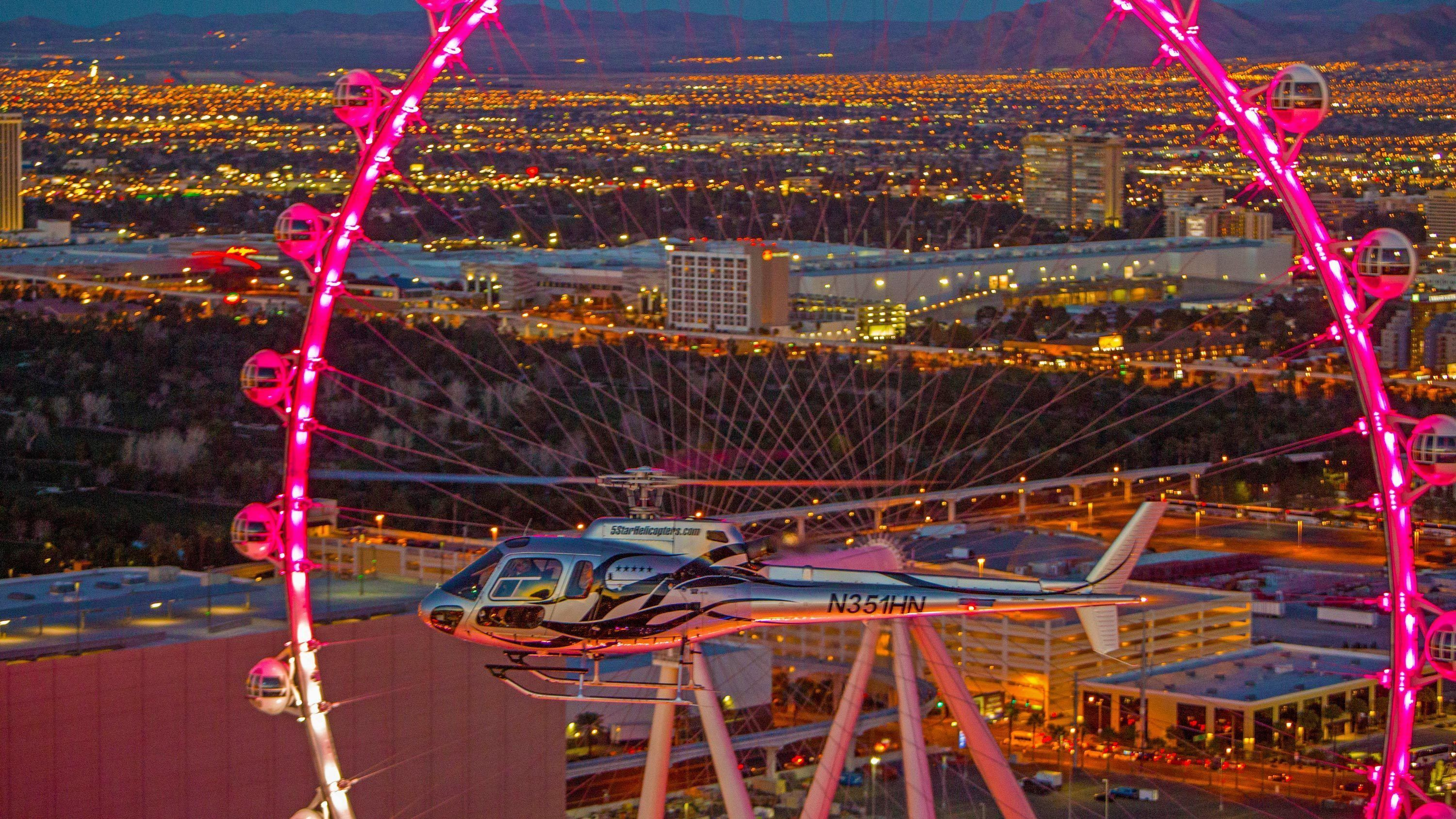 Helicopter near the High Roller ferris wheel at night in Las Vegas
