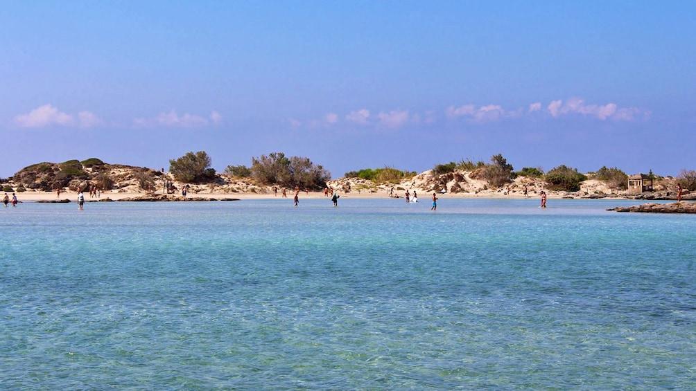 people walking through shallow beach water in Greece