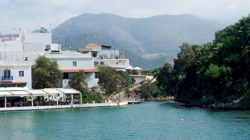 City with mountains in the distance as seen from the water off the coast of Crete Island