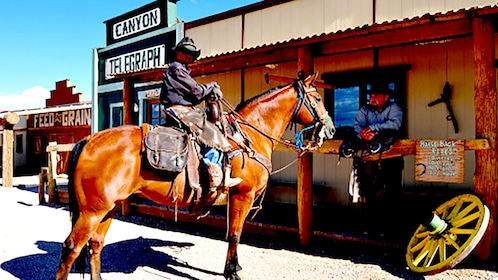 Cowboy on a horse hitched to a post outside a General Store in a Ghost Town