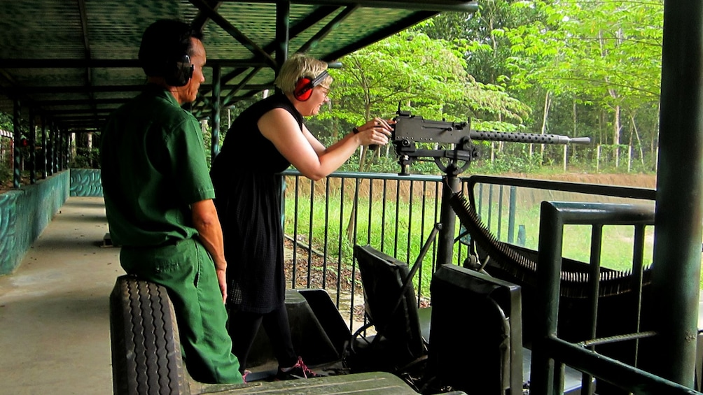 Show item 1 of 8. Woman shoots a machine gun on a gun range during Tour of Cu Chi Tunnels
