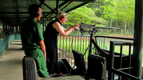 Woman shoots a machine gun on a gun range during Tour of Cu Chi Tunnels