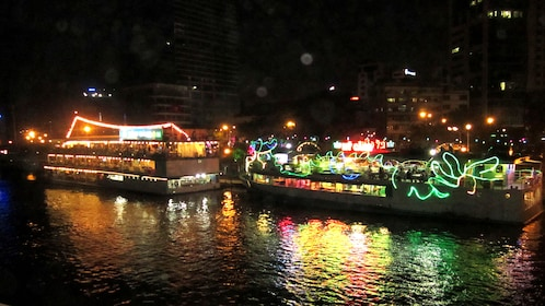Two riverboats covered in Christmas lights lit up at night