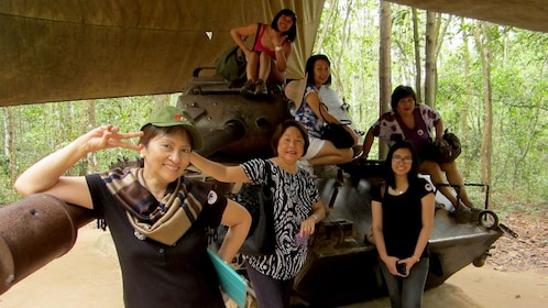 Six women pose on a decommissioned Tank under a canopy in Ho Chi Minh City