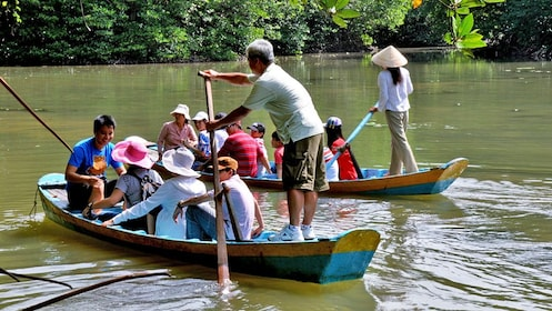Two tour groups in boats on a river in Vietnam