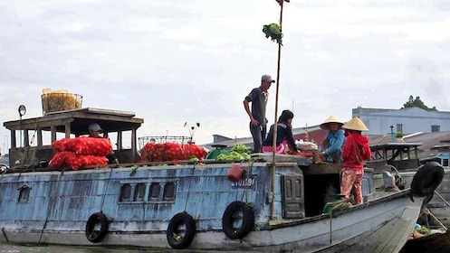A large boat full of produce in the Cai Be floating market