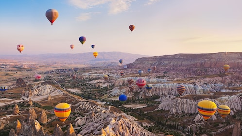 Tens of Hot Air Balloons floating in the air above the scenery of Istabul