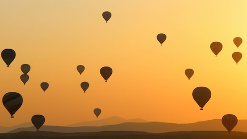 18 hot air balloons silhouetted in a yellowish dusk sky