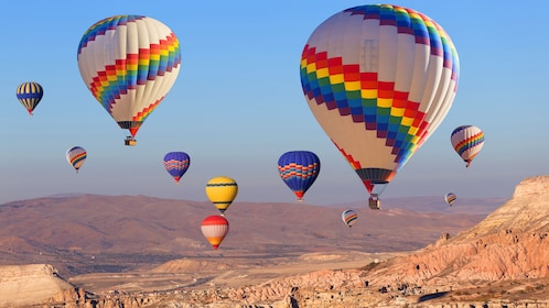 11 hot air balloons floating over a rocky landscape of Istanbul