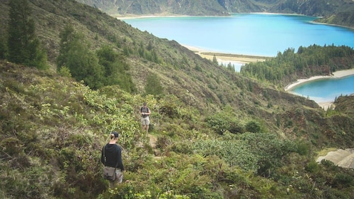 Group of people hiking down grassy hill surrounded by blue water.