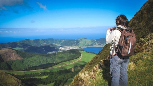 Hiker taking photo of beautiful view of area from elevated level.