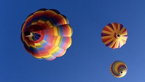 Three hot air balloons in a blue sky