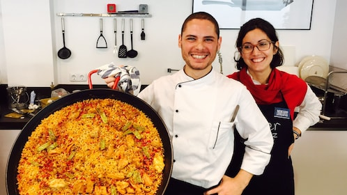 cooks with large paella pan