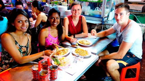 small group trying out different street foods in Bangkok
