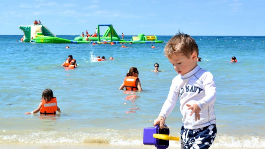 Show item 3 of 5. Young boy on the beach with water park in the distance.