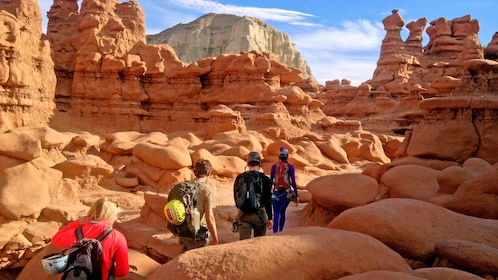 group hiking through naturally carved rock paths in Utah