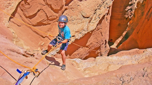 young climber descending into the rocky crevice in Utah