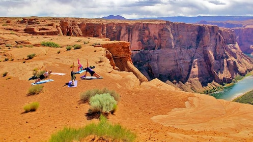 group practicing yoga near a steep cliff in Utah