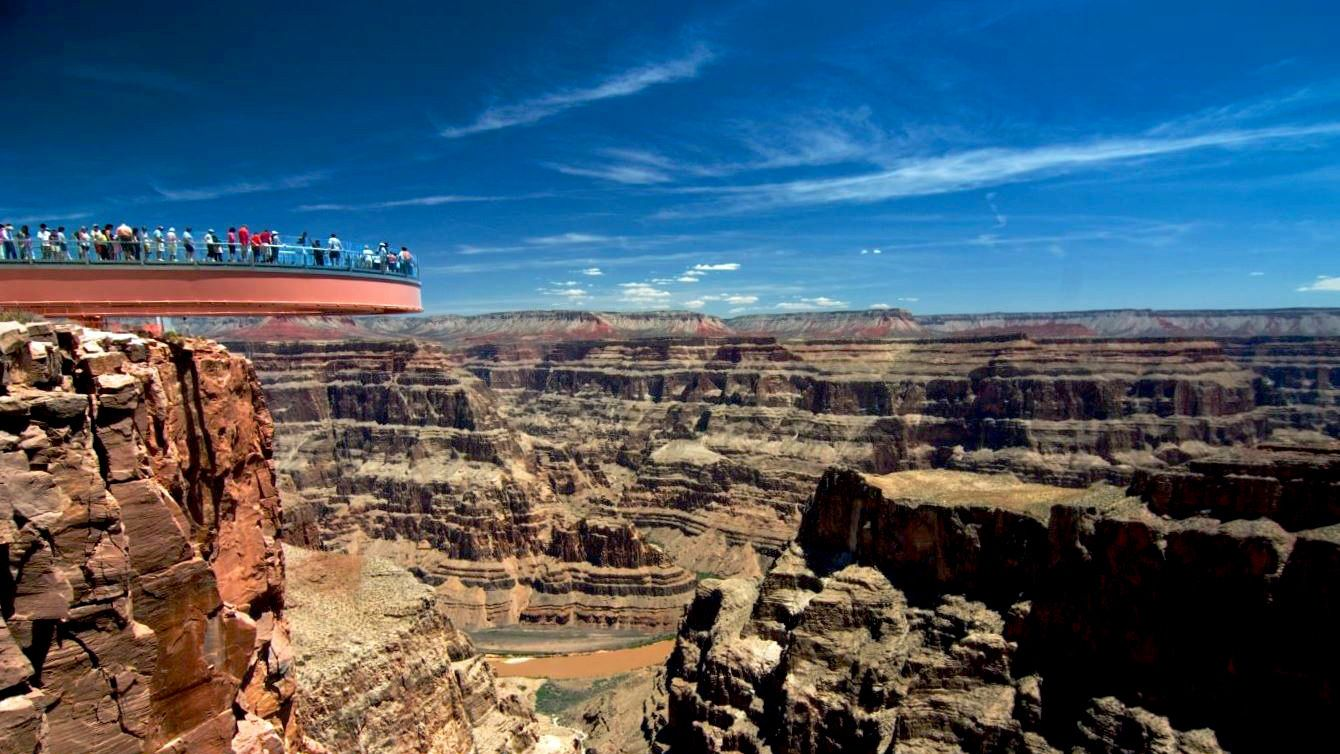 People stand on a Observation Deck over the Grand Canyon