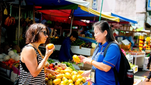 Woman with tour guide at a fruit market in Singapore