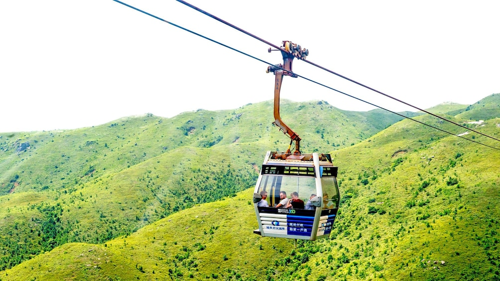 Show item 3 of 10. taking a gondola up the mountain in Lantau Island
