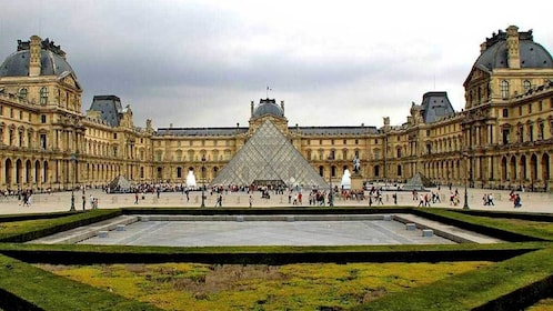 standing at the garden of the Louvre in Paris