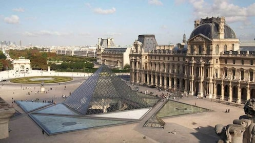 crowd scattered around the glass pyramid of the Louvre in Paris