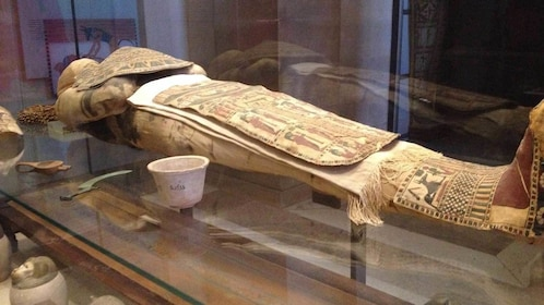 a preserved Egyptian mummy behind glass case at the Louvre in Paris