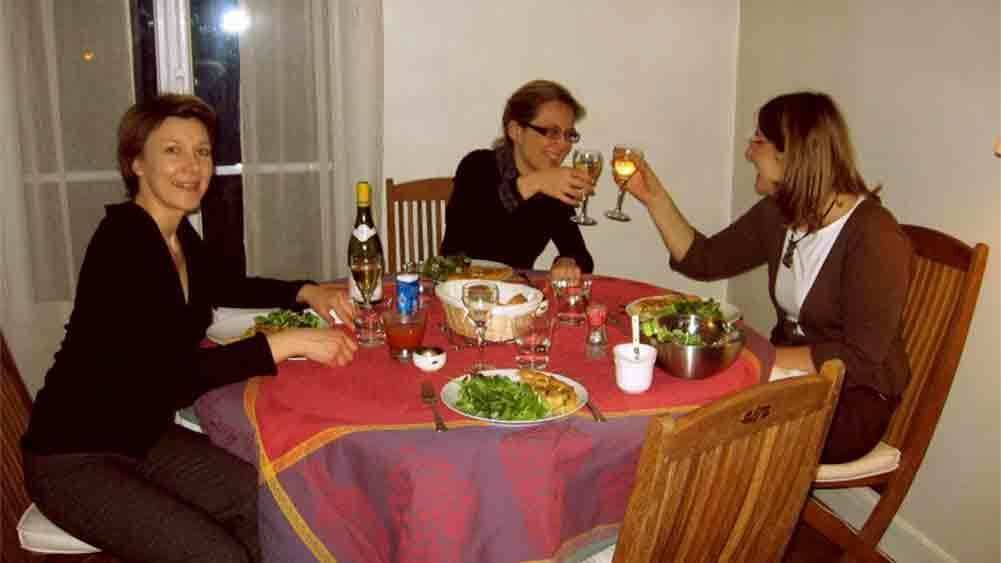 Women toasting with white wine at a table in a Parisian home