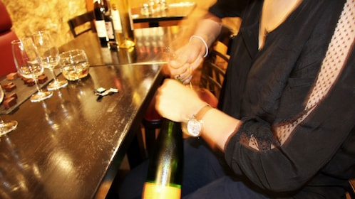 Woman opening a wine bottle at a bar in Paris