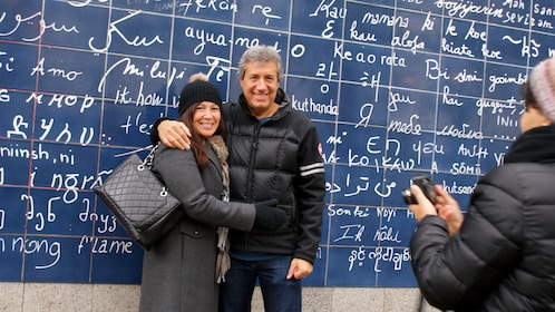 Couple posing for a photo in front of the I Love You Wall in Montmartre