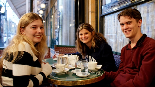 Three people sit at a table at Cafe De Flore