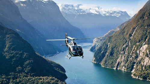 Serene view of a helicopter flying above the Milford Sound and Glaciers in New Zealand